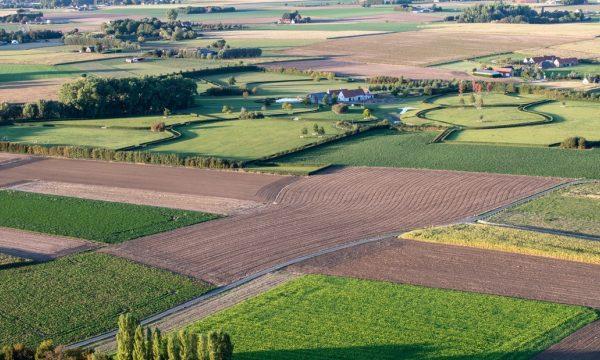 Luchtfoto van velden en een boerderij met een grote tuin