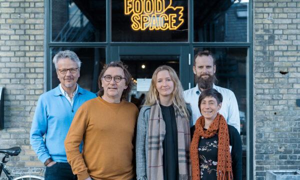 Groepsfoto van het team verantwoordelijk voor het Landbouwpark in Oostende. In de achtergrond 'Food Space' in neon letters