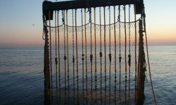 Pulsnet hangt half in het water bij een zonsondergang
