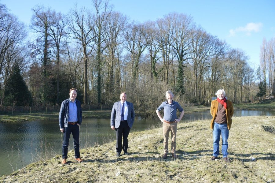 4 men standing on the bank of a river