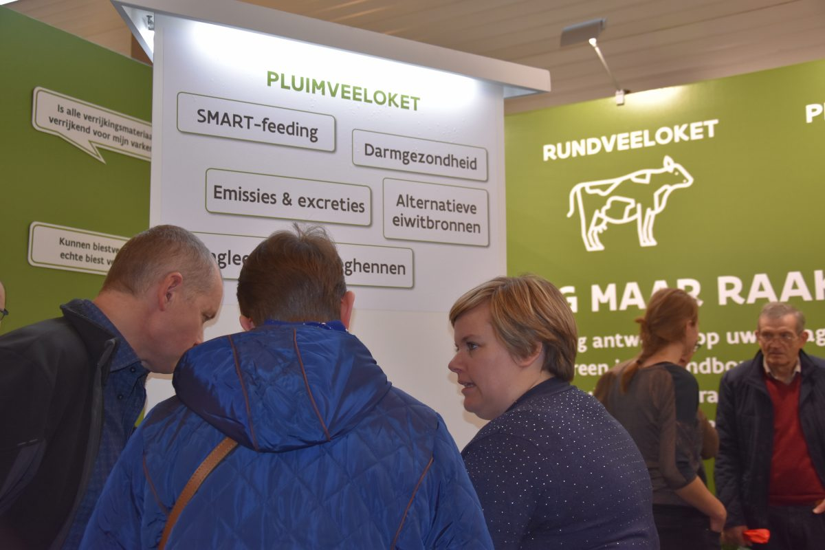 "Three people talking at a trade show in front of a poster saying ""pluimveeloket"""