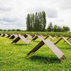 houten afdakjes in tentvorm op een gras-klaver veld