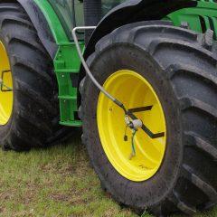 Tractor met grote tractorbanden op een grasakker