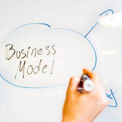 een hand schrijft op een whiteboard het woord business model in een cirkel met pijlen errond