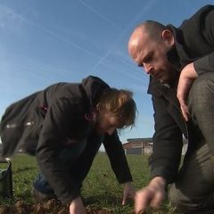 twee ILVO onderzoekers op het veld, met hun handen in de aarde. ze nemen een bodemstaal.