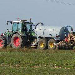 Een landbouwer rijdt mest uit met mestinjectie