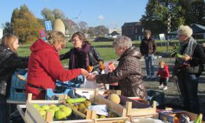 een fruitkraam waar een consument iets koopt van een handelaar en haar zakje meekrijgt