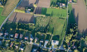 Luchtfoto van een Vlaamse lintbebouwing met huizen en erachter tuinen die het achterliggende landschap afsnijden en afboorden