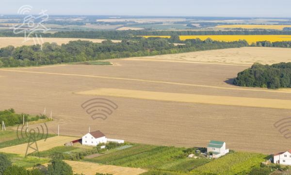 Het platteland met enkele huizen, pictogrammen van een zendmast, wifi en een drone