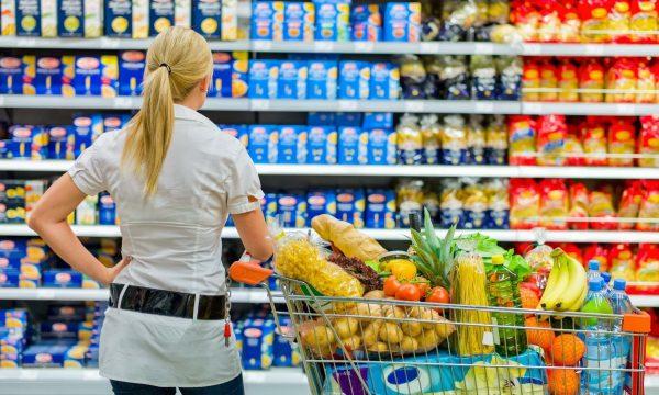 Een consument staat voor een winkelrek en twijfelt over haar keuze.