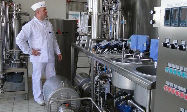 Persoon in witte kledij inspecteert apparatuur van de Food Pilot