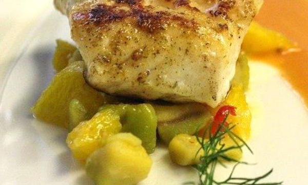 Een mooi gedresseerd bord met een stukje gebakken kabeljauw op een bedje van groenten.
