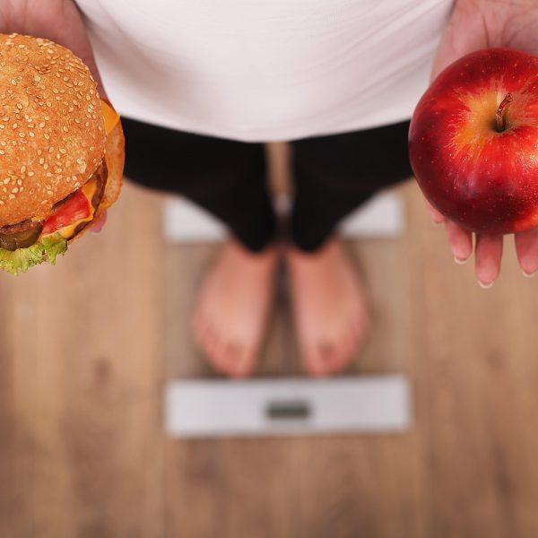 Een persoon op een weegschaal vergelijkt een hamburger en een appel