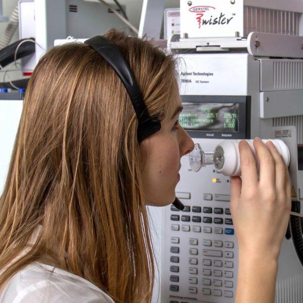 Een vrouw zit in een labo met haar neus aan een toestel dat aroma verspreidt