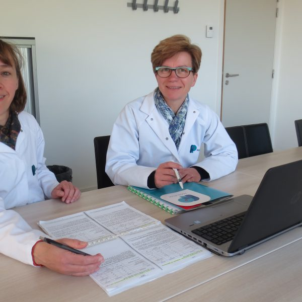 Two smiling women in lab coats seated at a table with a computer and papers