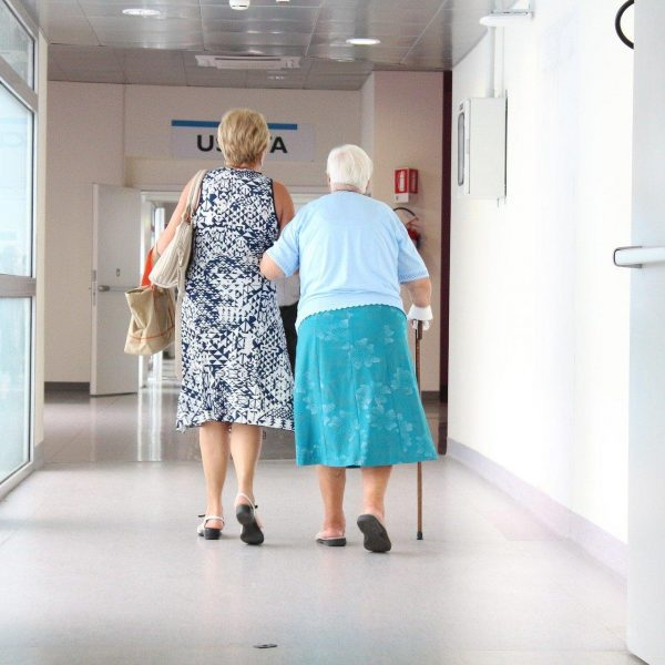 Young person and old person walking in hospital corridor