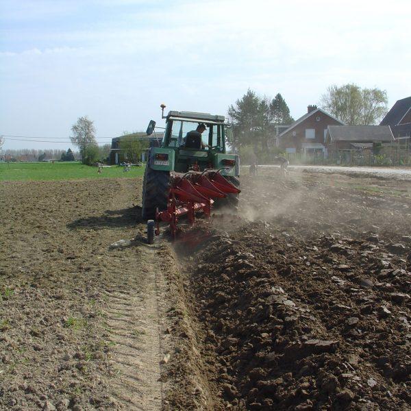 Een landbouwer past maaimeststoffen toe op een akker