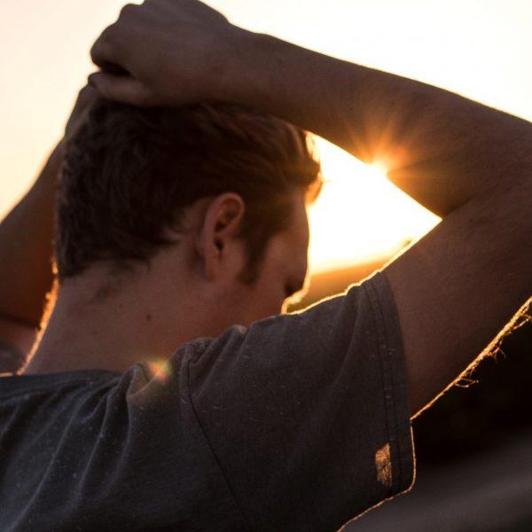 Foto van jonge boer die met beide handen het hoofd vasthoudt in diepe stress