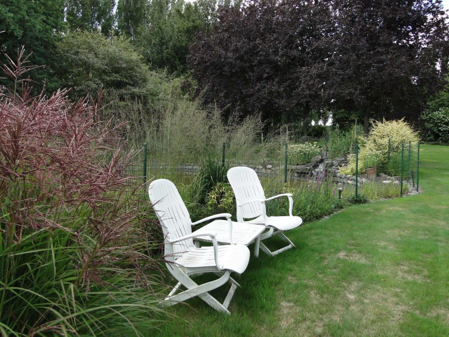 Lawn chairs with vegetable garden behind them